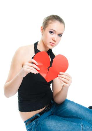 A girl shows a broken heart made of paper photo