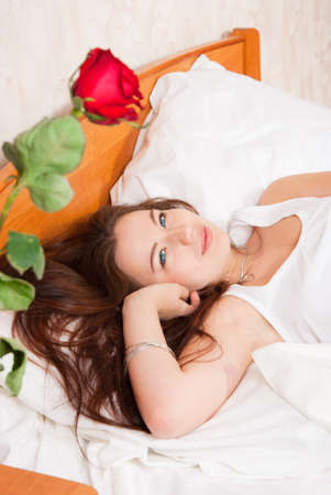 The girl saw a rose in the morning in bed Stock Photo - 11312491