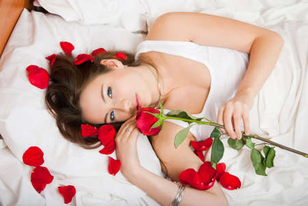 Woman lying in bed with a rose photo