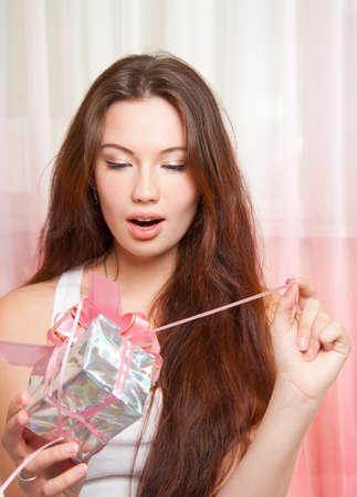 Surprised beautiful girl unpacks gift Stock Photo - 11312487
