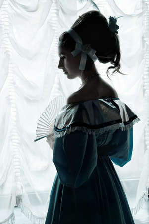 respectable: A girl stands at the window Stock Photo