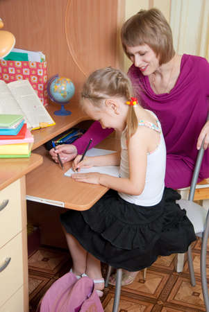Mom helps daughter make the lessons photo