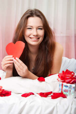 adult valentine: Portrait of a beautiful girl with a valentine in the hands of the bed Stock Photo