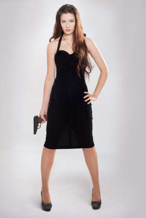 The girl with a pistol costs having lowered hands Stock Photo - 12029050