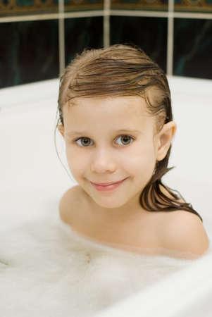 little girl bath: A child swims in the bathtub