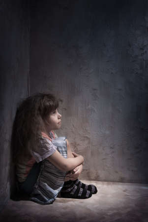 child alone in a dark corner photo
