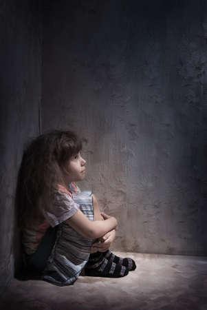 child alone in a dark corner Stock Photo