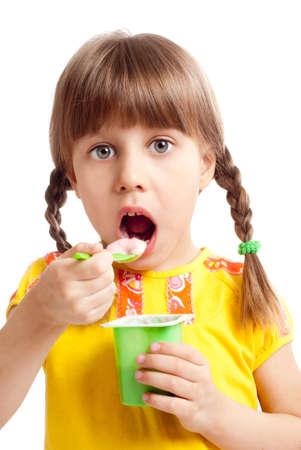 Little child eating yogurt Foto de archivo