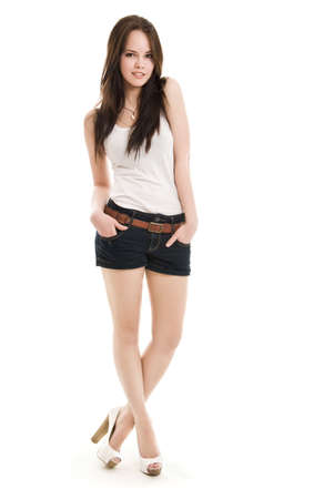 The girl in shorts standing on a white background Foto de archivo