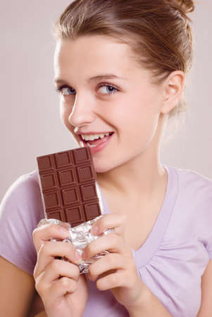 portrait smiling young woman eating a chocolate bar photo