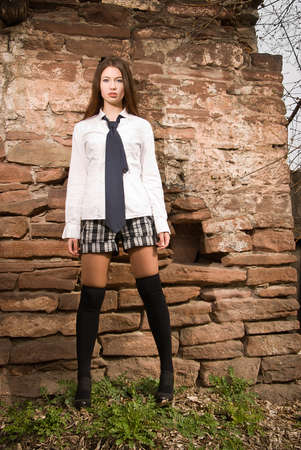 A girl stands near the old wall photo