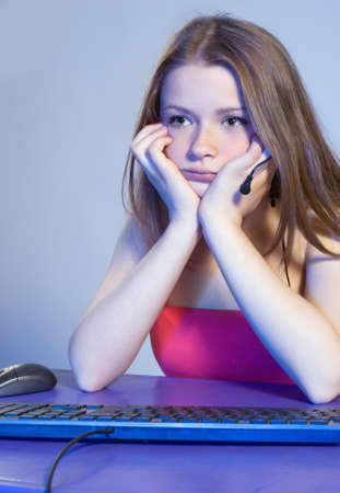 Tired teenage girl in front of a computer monitor
