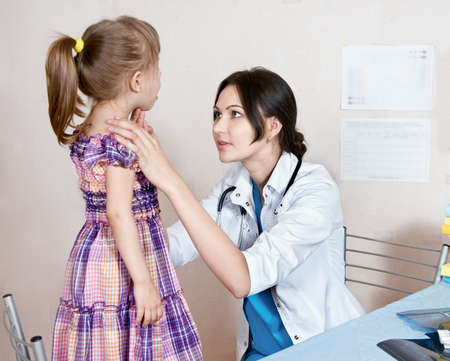 The doctor examines the child's throat Stock Photo