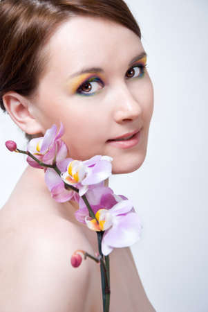 Beautiful girl's face and orchid Stock Photo - 13619282
