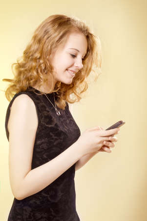 Young girl with mobile phone, a yellow background photo