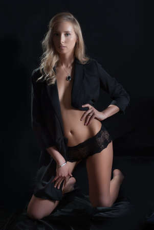 The girl nude girl in a jacket on a black background Stock Photo - 13921306