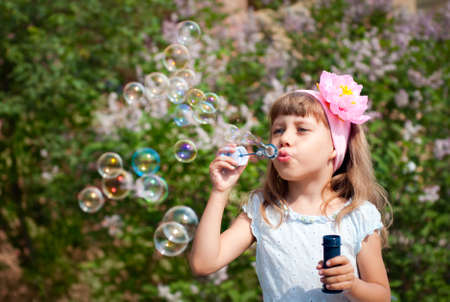 Portrait of funny lovely little girl blowing soap bubbles photo
