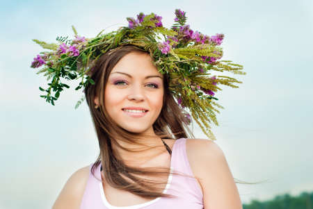 Beautiful brunette girl in a wreath of wild flowers photo