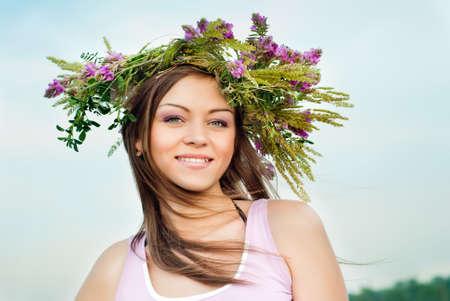 Beautiful brunette girl in a wreath of wild flowers photo