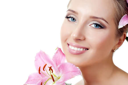 The face of a beautiful girl with a fresh flower lily photo
