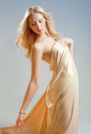 Beautiful seductive girl in golden drapery photo