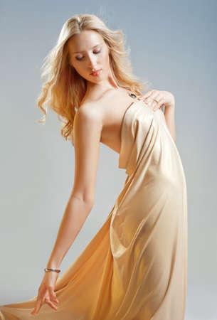 Beautiful seductive girl in golden drapery Stock Photo