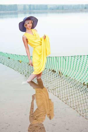 A girl stands in the water near the fishing nets photo