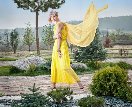 The girl in the park in a yellow dress photo