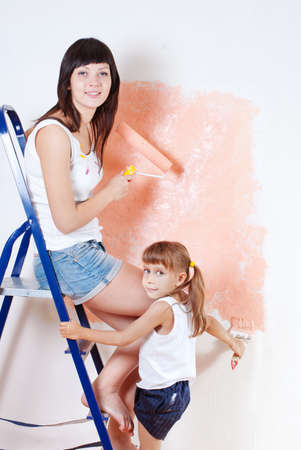 The woman and the child paint the wall on the ladder photo
