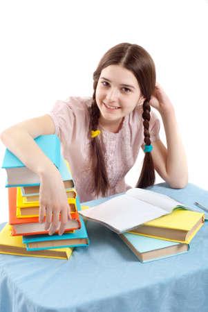 prodigio: Il bambino ragazza al tavolo con libri su sfondo bianco Archivio Fotografico