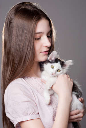 Teen girl holding a white kitten photo