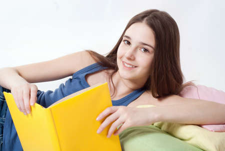 Teenager girl lying down reading a book photo