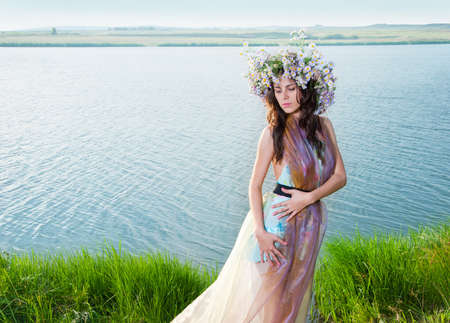 The girl in the wreath stands against the backdrop of beautiful scenery photo