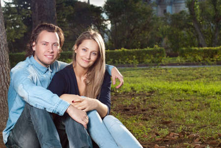 couple on a walk, sit on the grass in the park photo