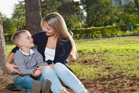 Mom and her son enjoyed the walk, sitting on the grass Stock Photo - 15036828