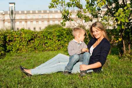 Mom and her son enjoyed the walk, sitting on the grass Stock Photo - 15278093