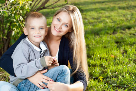 Mom and her son enjoyed the walk, sitting on the grass Stock Photo - 15278095