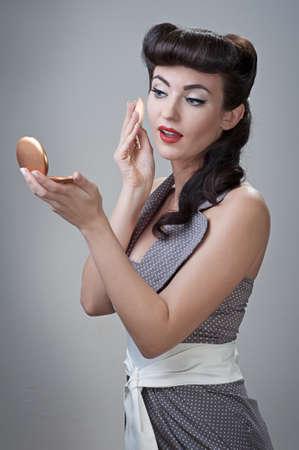young beautiful caucasian girl powders her face, retro styling Standard-Bild