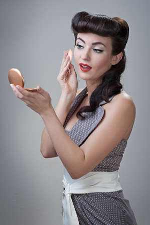 young beautiful caucasian girl powders her face, retro styling Stock Photo