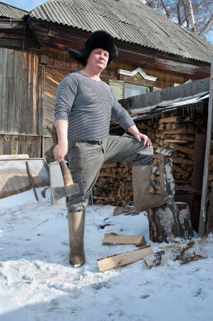 ax man: A man with an ax near the country house in winter