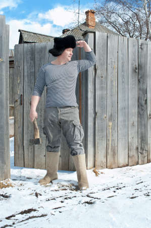 A man with an ax near the country house in winter photo