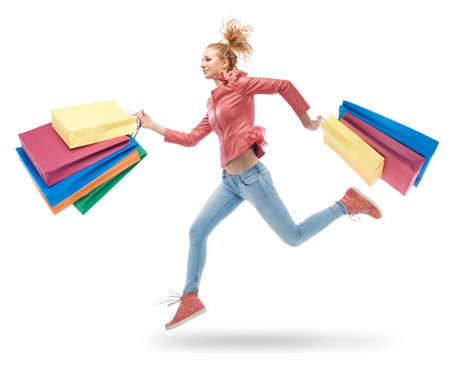 young woman running with shopping bags in hands photo
