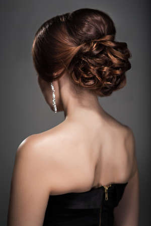 womans: Woman in evening dress with beautiful hairstyle from the back
