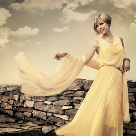 A young girl in a yellow dress in the park photo