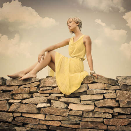 The girl is sitting on a stone wall against the blue cloudy sky photo