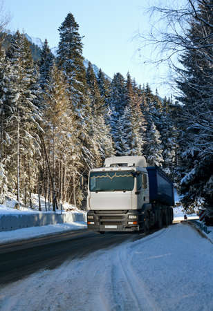 Spruce in the snow in winter forest , truck on a winter road  photo