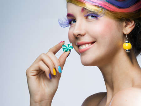Girl with bright makeup eating candy  photo