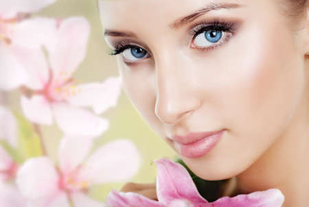 womanliness: The face of a beautiful girl with a fresh flower lily Stock Photo