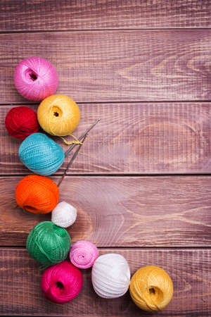 Balls of colored yarn on wooden boards photo
