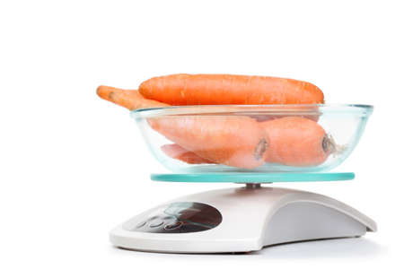 Kitchen weight scale with carrots. Isolated on white background.  photo
